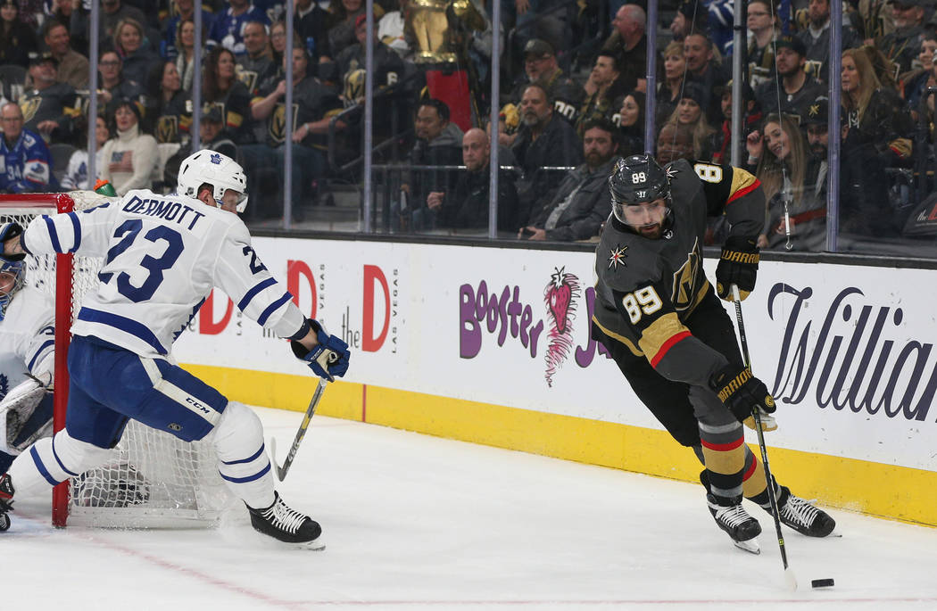 Vegas Golden Knights right wing Alex Tuch (89) skates with the puck as Toronto Maple Leafs defenseman Travis Dermott (23) guards him during the first period of an NHL hockey game at T-Mobile Arena ...
