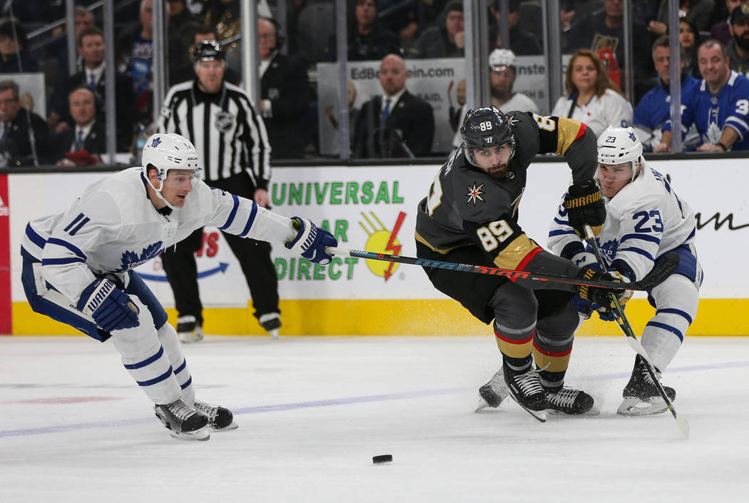 Vegas Golden Knights right wing Alex Tuch (89) battles Toronto Maple Leafs left wing Zach Hyman (11), left, and Toronto Maple Leafs defenseman Travis Dermott (23) for the puck during the third per ...