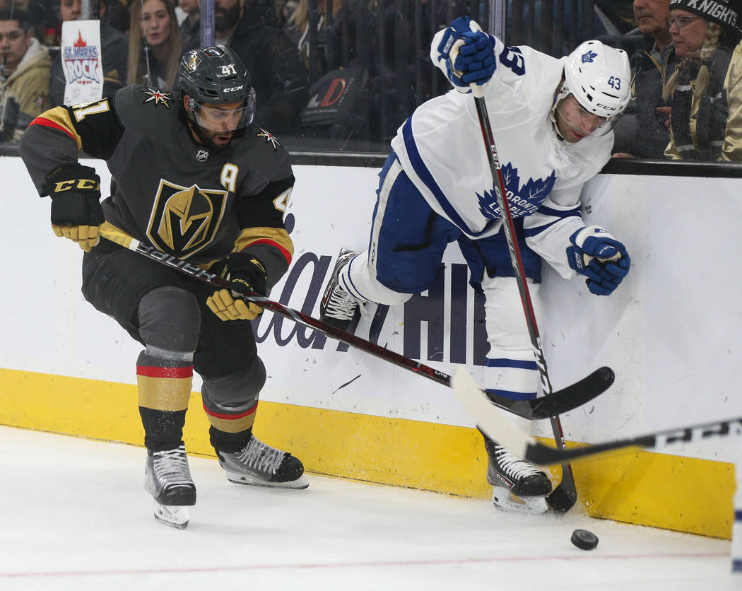 Vegas Golden Knights center Pierre-Edouard Bellemare (41) and Toronto Maple Leafs center Nazem Kadri (43) fight for the puck during the first period of an NHL hockey game at T-Mobile Arena in Las ...