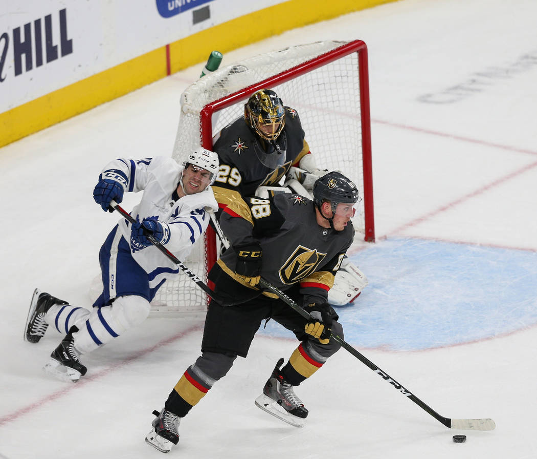 Vegas Golden Knights defenseman Nate Schmidt (88) skates with the puck while under pressure from Toronto Maple Leafs defenseman Jake Gardiner (51) during the second period of an NHL hockey game at ...