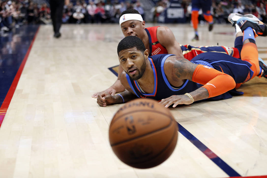 Oklahoma City Thunder forward Paul George, front, and New Orleans Pelicans guard Tim Frazier watch the ball go out of bounds during the first half of an NBA basketball game in New Orleans, Thursda ...