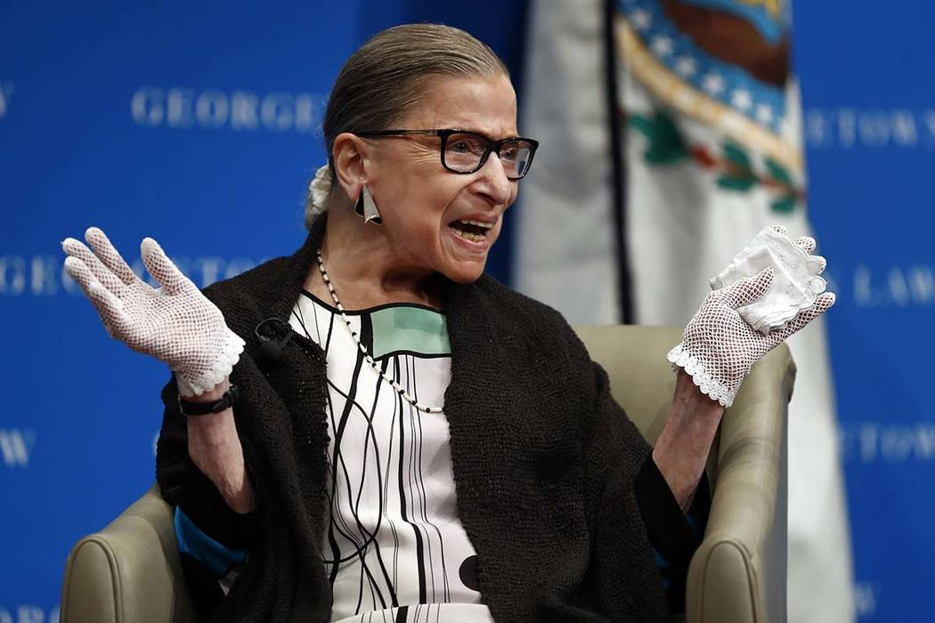 In this Sept. 20, 2017 photo, U.S. Supreme Court Justice Ruth Bader Ginsburg reacts to applause as she is introduced by William Treanor, Dean and Executive Vice President of Georgetown University ...