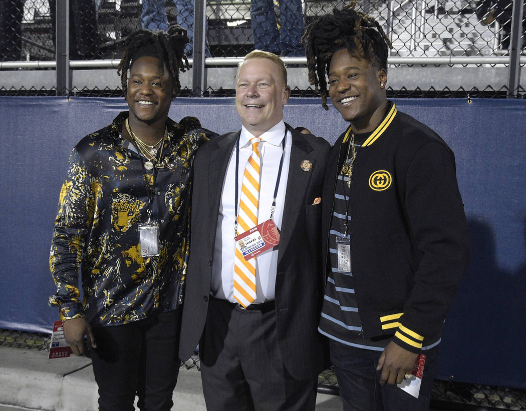 Orlando Apollos president Michael Waddell, center, poses on the sideline with Seattle Seahawks linebacker Shaquem Griffin, left, and defensive back Shaquill Griffin during the first half of the te ...