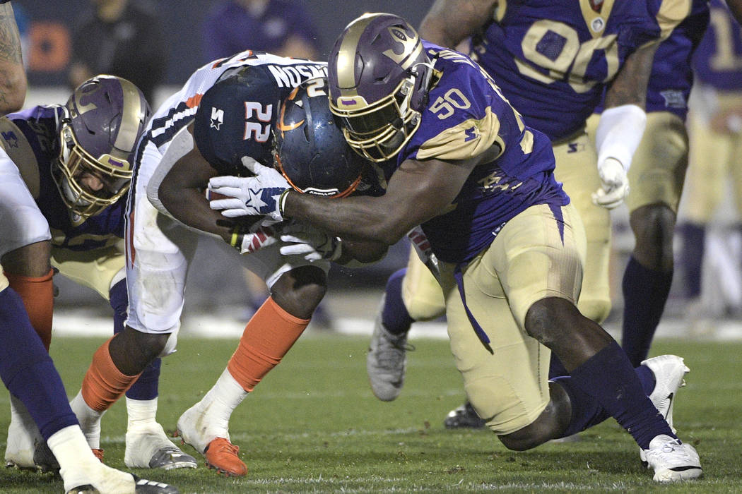 Orlando Apollos running back D'Ernest Johnson (22) is stopped by Atlanta Legends linebacker Jeff Luc (50) after rushing for a short gain during the first half of an Alliance of American Football g ...