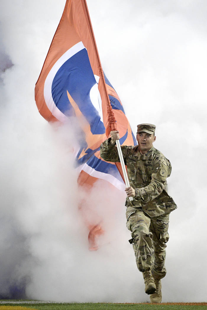 A member of the U.S. military carries a team flag onto the field before an Alliance of American Football game between the Orlando Apollos and the Atlanta Legends on Saturday, Feb. 9, 2019, in Orla ...