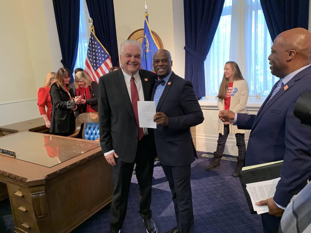 Gov. Steve Sisolak, left, and Senate Majority Leader Kelvin Atkinson, D-North Las Vegas, the prime sponsor of Nevada's new law requiring background checks for private gun sales, pose with the bill ...
