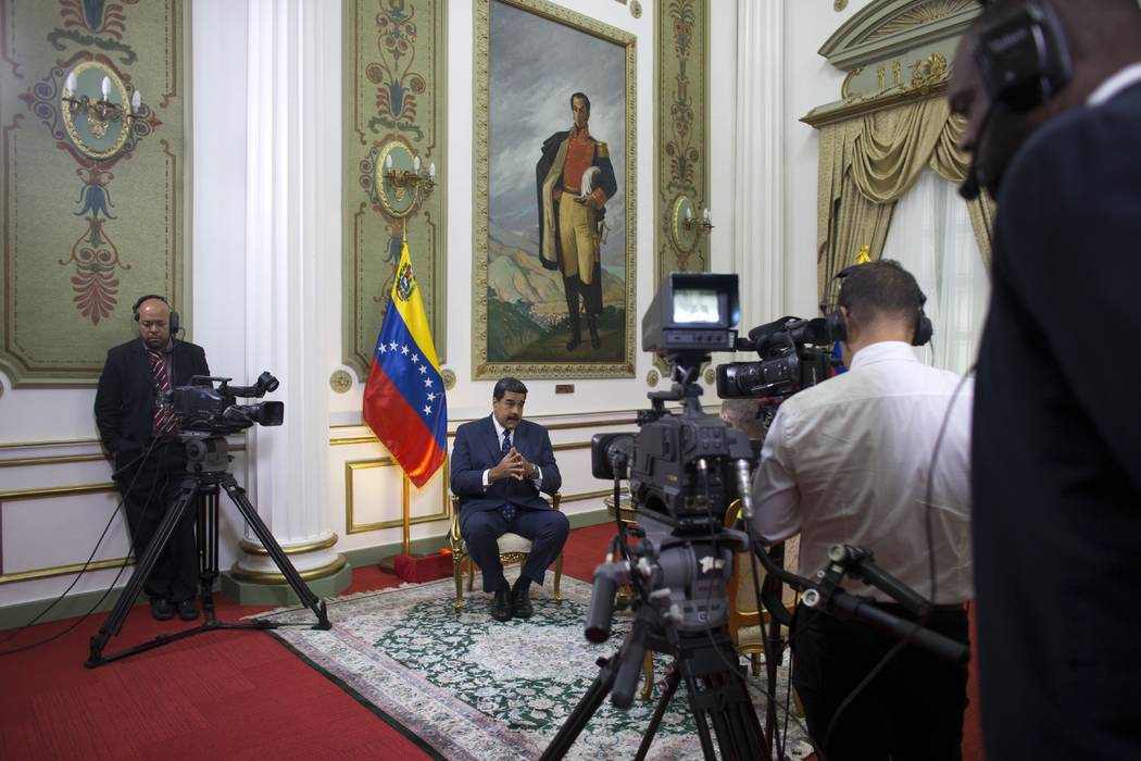 Venezuela's President Nicolas Maduro speaks during an interview with The Associated Press at Miraflores presidential palace, where a painting of independence hero Simon Bolivar hangs, in Caracas, ...