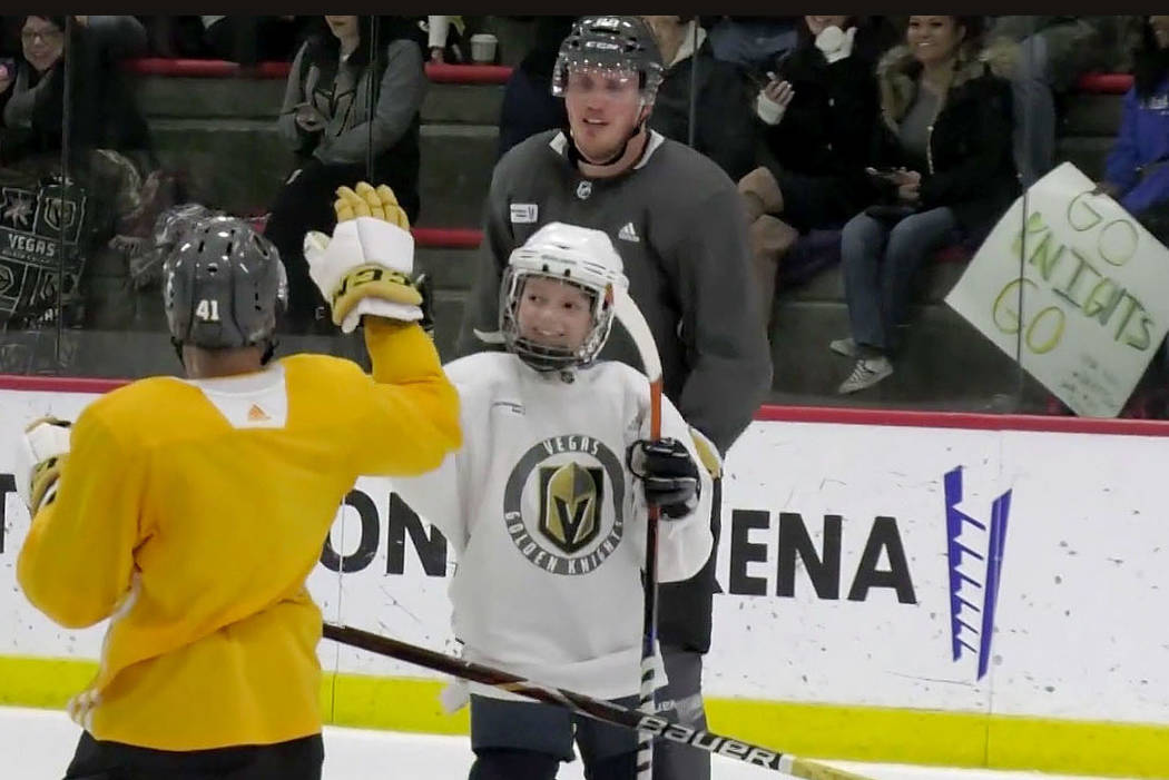 Vegas Golden Knights center Pierre-Edouard Bellemare (41) gives honorary Golden Knights player Jace Owen, 8,, right, a high-five during a practice at City National Arena in Las Vegas, Friday, Feb. ...