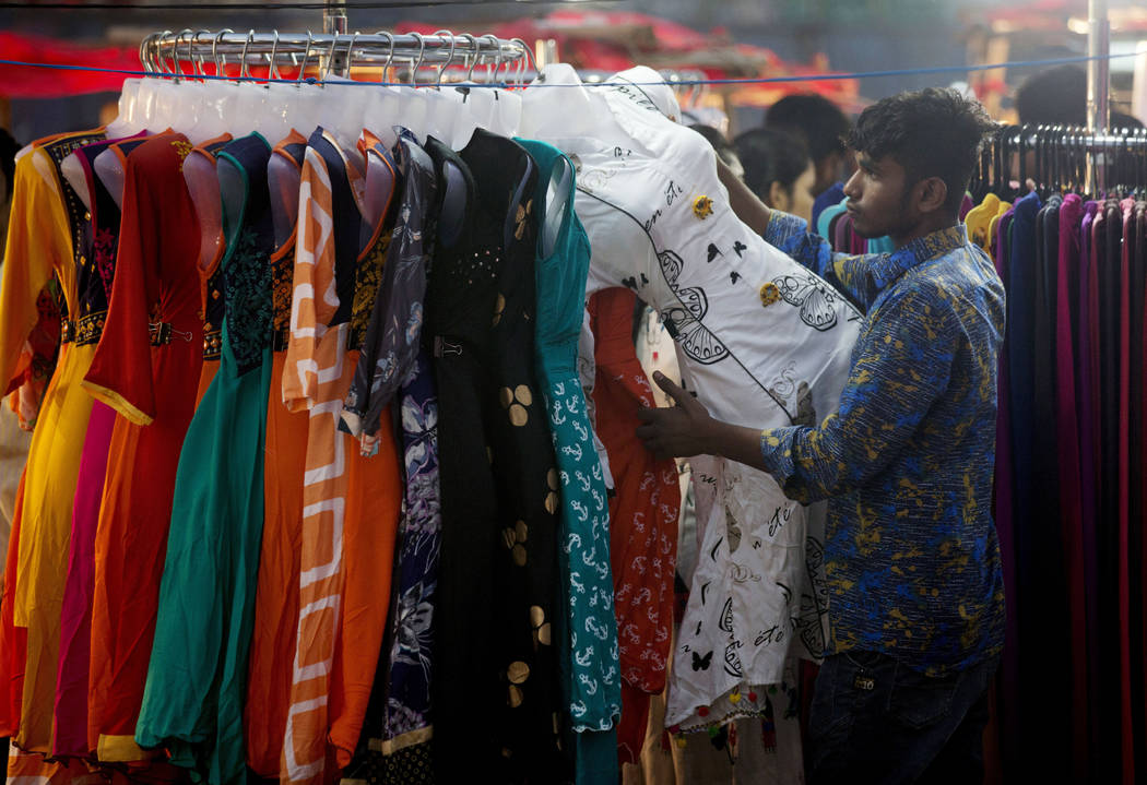 An Indian clothes vendor arranges his display as he awaits customers in the old city area of Hyderabad, India, Wednesday, Feb.6, 2019. (AP Photo /Mahesh Kumar A.)