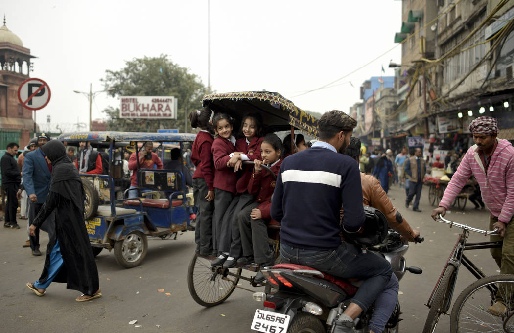 Indian children ride on a cycle rickshaw on their way back from school in the old quarters of New Delhi, India, Thursday, Feb. 7, 2019. (AP Photo/R S Iyer)