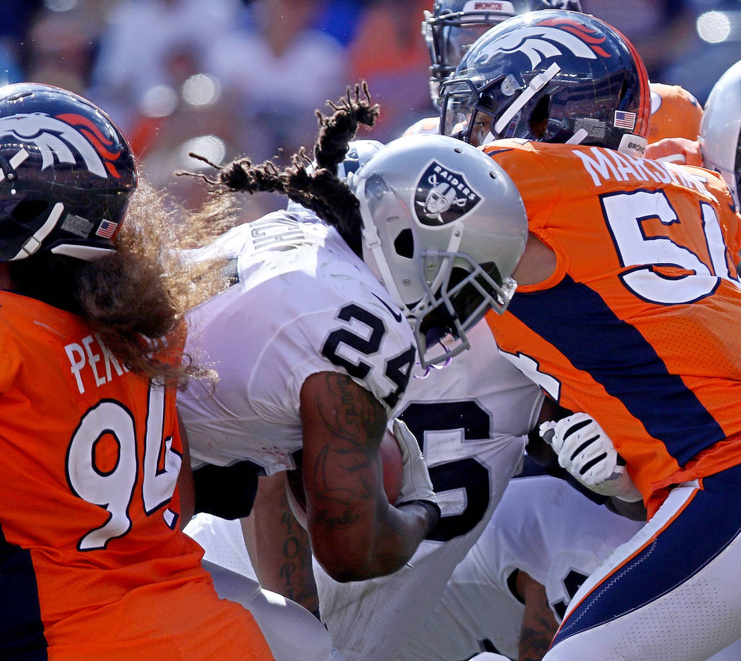 Oakland Raiders running back Marshawn Lynch (24) leaps in to the end zone for a touchdown as Denver Broncos linebacker Brandon Marshall (54) tries to stop him during the first half of their NFL ga ...