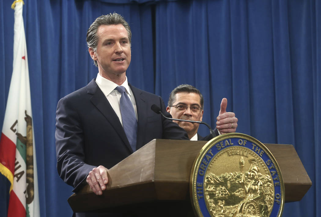 California Gov. Gavin Newsom, left, flanked by Attorney General Xavier Becerra, right, answers a question concerning a lawsuit the state will likely file against President Donald Trump over his e ...