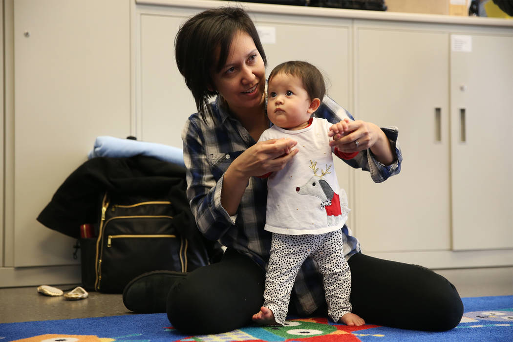 """Melanie Bartels with her 9-month-old daughter Videl participate during a dance and activity class, """"Tiny Toes on the Go,""""at the Clark County Library in Las Vegas, Friday, Feb. 15, 2019. ..."""