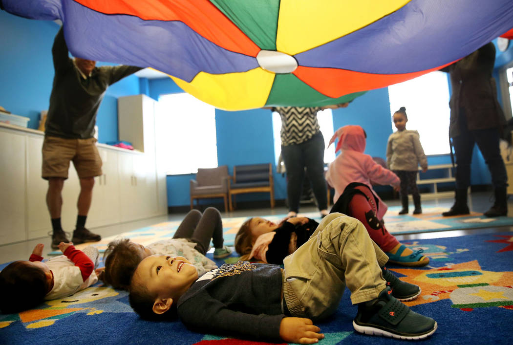 """Angelo Karvonen-Martinez, 2, of Las Vegas, looks up at a parachute during a dance and activity class, """"Tiny Toes on the Go,"""" at the Clark County Library in Las Vegas, Friday, Feb. 15, 20 ..."""