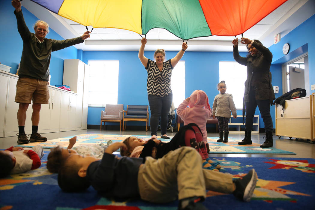 """Dave Cooley, from left, Chantalle Uzan, and Keisha Liu with her daughter Brooklyn Ramos, 3, play with a parachute during a dance and activity class, """"Tiny Toes on the Go,""""at the Clark Co ..."""