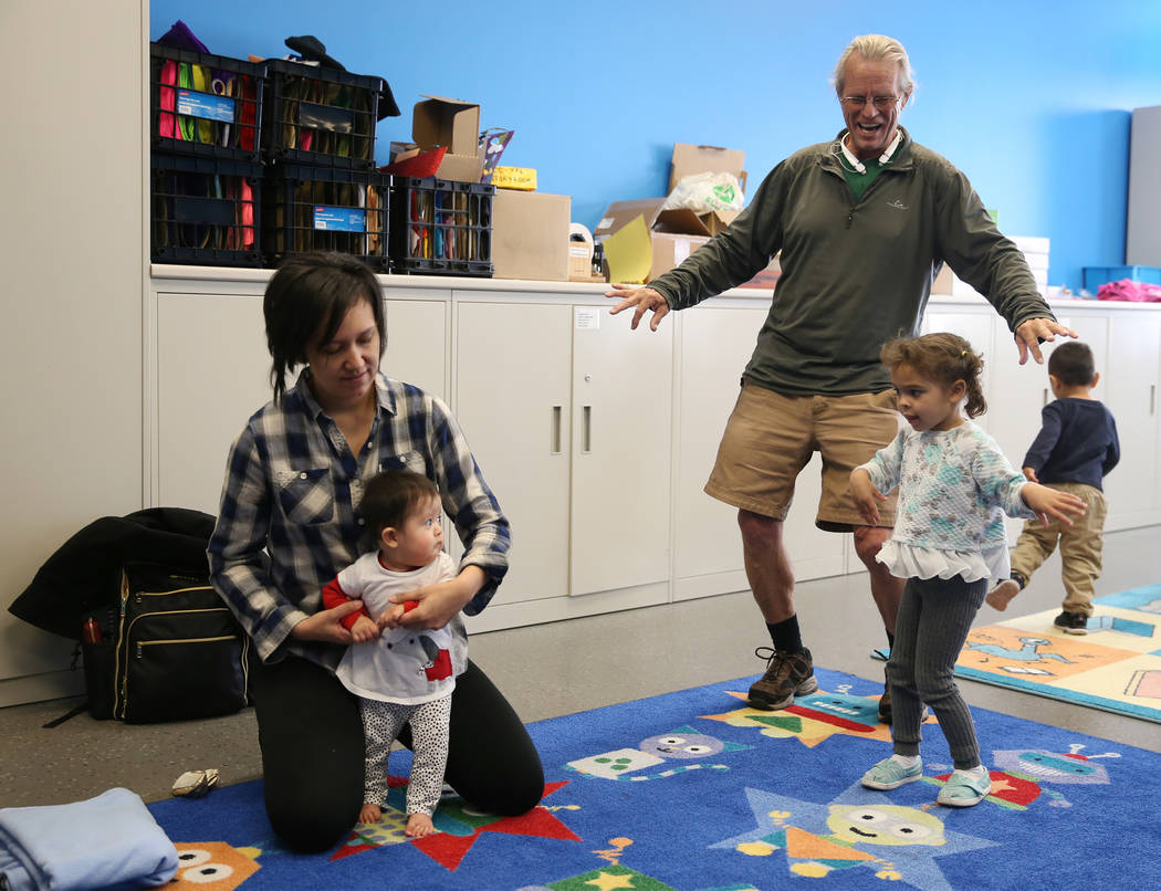 """Melanie Bartels, with 9-month-old daughter Videl, and Dave Cooley with his granddaughter Ruby Jo Arnold, 3, participate during a dance and activity class, """"Tiny Toes on the Go,""""at the Cl ..."""