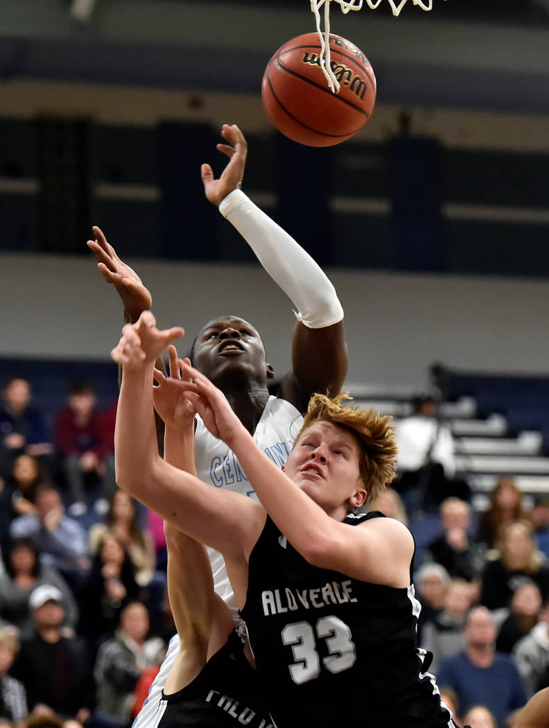 Centennial's Leland Wallace (15) and Palo Verde's Sam Johnson (33) reach for a rebound during a high school basketball game at Centennial High School Friday, Feb. 15, 2019, in Las Vegas. (David Be ...
