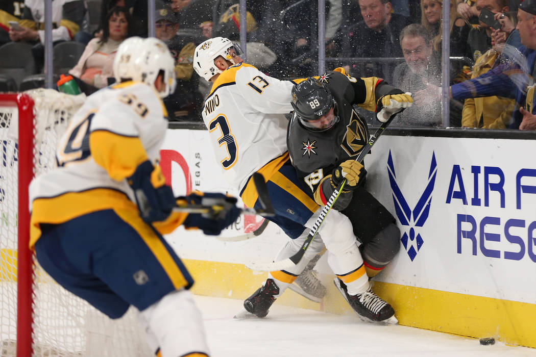 Vegas Golden Knights right wing Alex Tuch (89) takes a hit from Nashville Predators center Nick Bonino (13) during the first period of an NHL hockey game at T-Mobile Arena in Las Vegas, Saturday, ...