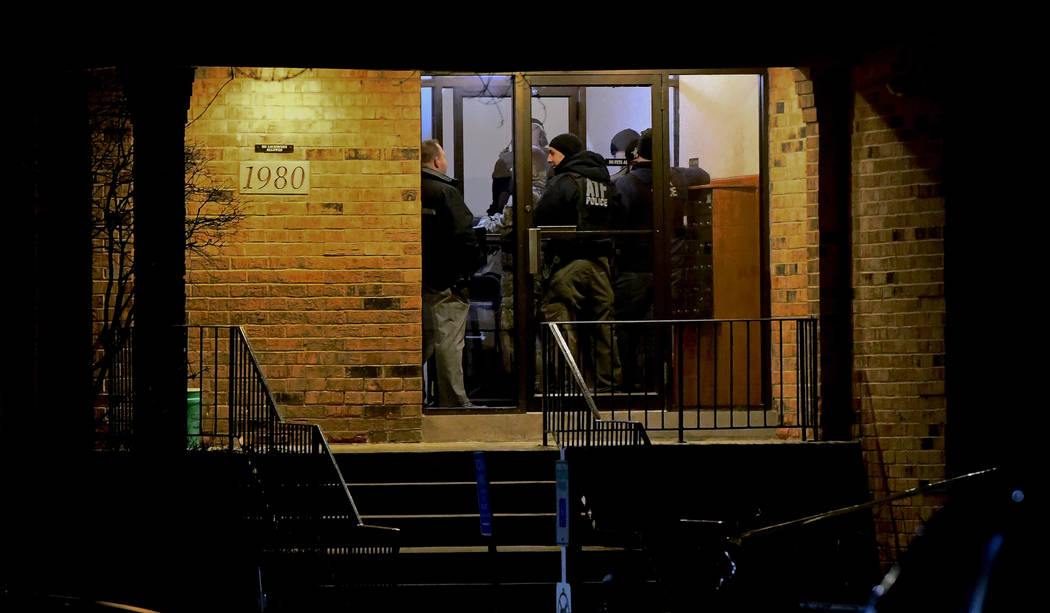 Investigators enter an apartment building Friday, Feb. 15, 2019, in Aurora, Ill., where a man who police say fatally shot several people and injured police officers at a manufacturing plant in Aur ...