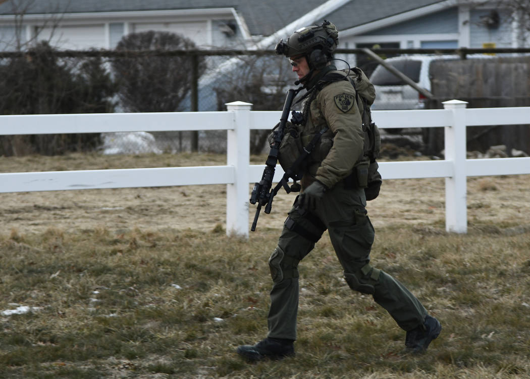 A law enforcement officer works at the scene of a shooting at the Henry Pratt Co. on Friday, Feb. 15, 2019, in Aurora, Ill. Officials say several people were killed and at least five police office ...