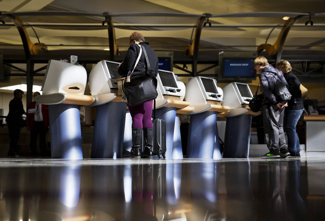 FILE - In this Jan. 30, 2017 file photo, passengers check in for Delta Air Lines flights at kiosks at Hartsfield-Jackson Atlanta International Airport in Atlanta. Major U.S. airlines say they will ...