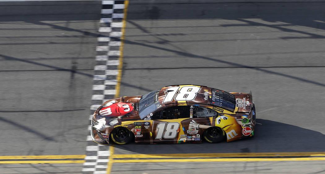 Kyle Busch (18) crosses the line to win the first stage of a NASCAR Daytona 500 auto race Sunday, Feb. 17, 2019, at Daytona International Speedway in Daytona Beach, Fla. (AP Photo/Chris O'Meara)