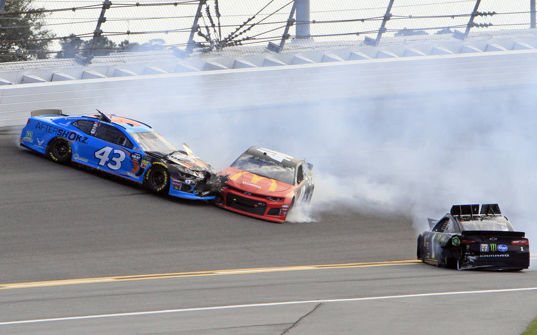 Jamie McMurray, center, crashes into Darrell Wallace Jr. (43) after Kurt Busch, right, spins out from the wreck during the NASCAR Daytona 500 auto race at Daytona International Speedway, Sunday, F ...