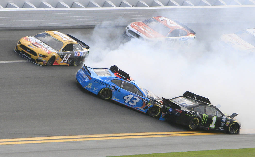 Darrell Wallace Jr. (43) gets caught up in a wreck with Kurt Busch (1) as Clint Bowyer (14) goes high to avoid the crash during a NASCAR Daytona 500 auto race at Daytona International Speedway, Su ...