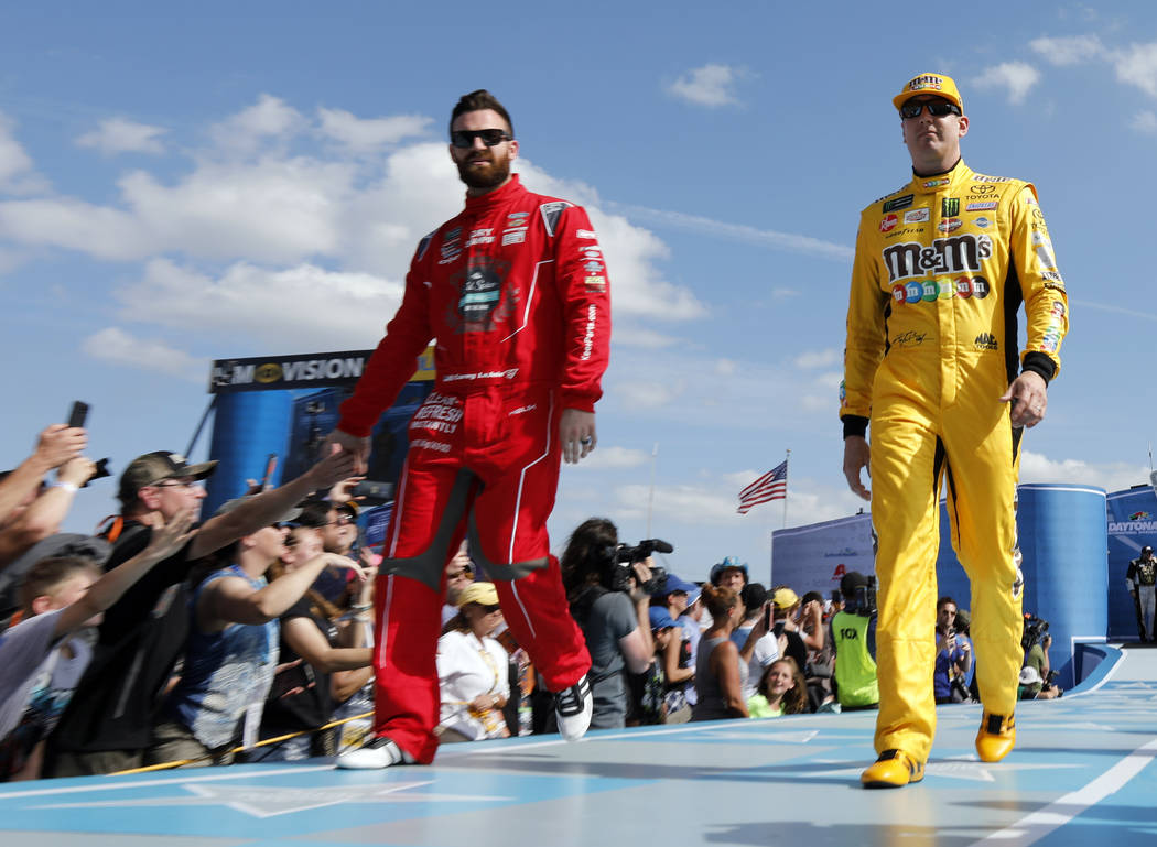 Corey LaJoie, front left, and Kyle Busch greet fans during driver introductions before the NASCAR Daytona 500 auto race at Daytona International Speedway, Sunday, Feb. 17, 2019, in Daytona Beach, ...