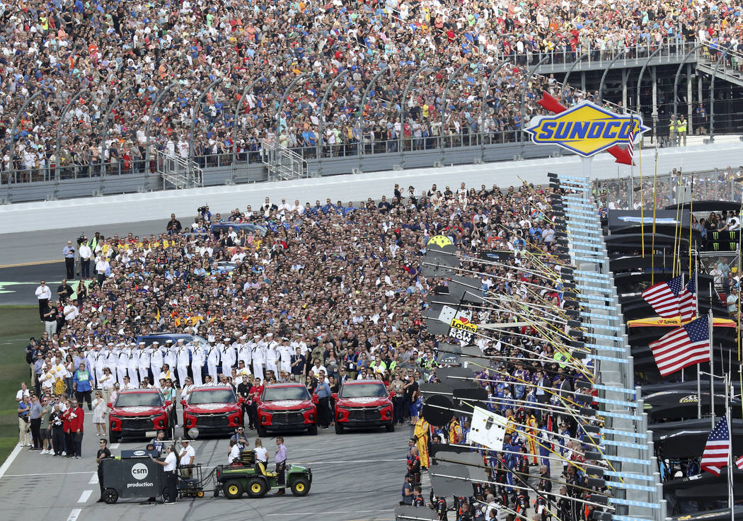Members of the military, race crews and fans gather on pit road during the national anthem before the start of the NASCAR Daytona 500 auto race at Daytona International Speedway, Sunday, Feb. 17, ...