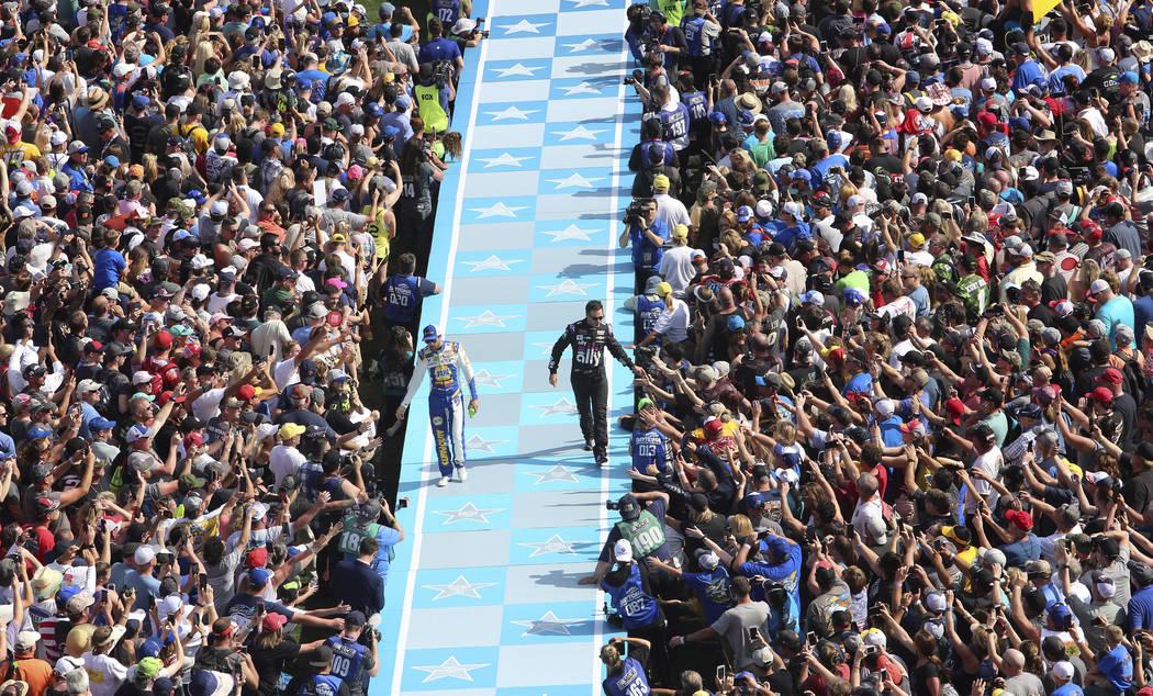 Chase Elliott, left, and Jimmie Johnson greet fans during driver introductions before the NASCAR Daytona 500 auto race at Daytona International Speedway, Sunday, Feb. 17, 2019, in Daytona Beach, F ...
