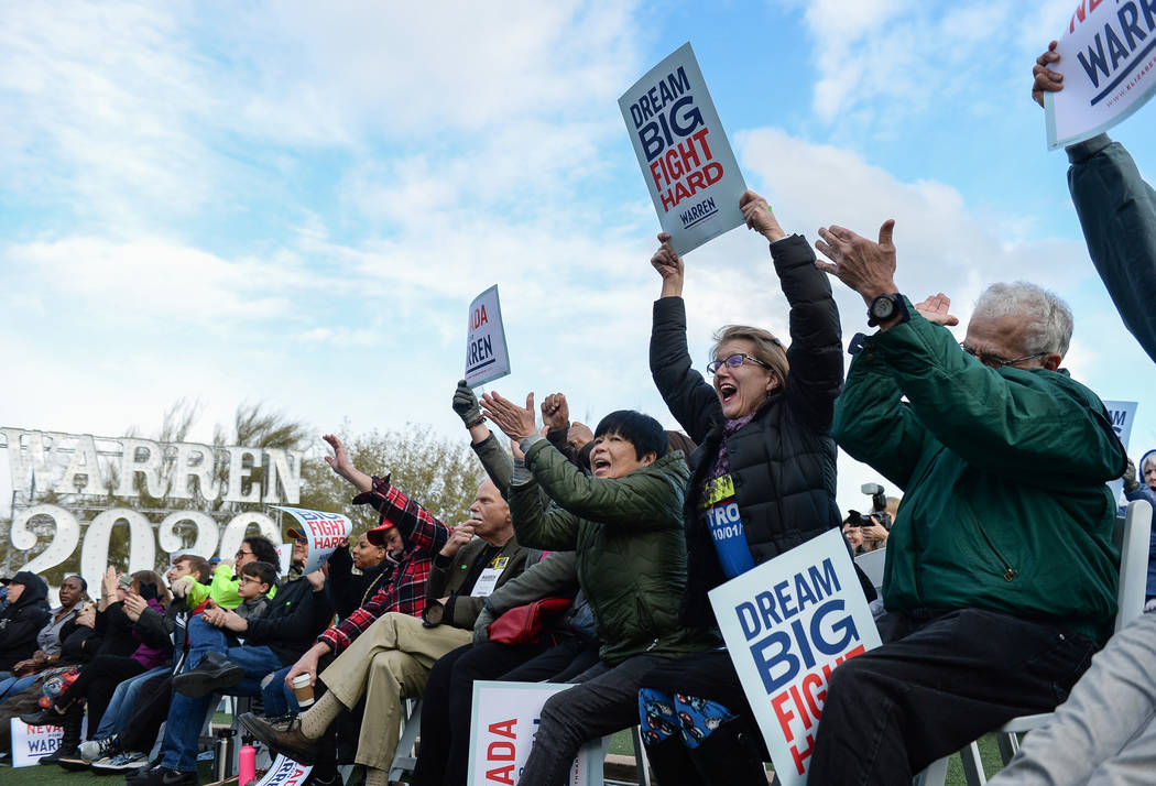 People cheer as they are gathered to watch Elizabeth Warren deliver a speech about her platform to run for President of the United States in 2020 at Springs Preserve in Las Vegas, Sunday, Feb. 17, ...