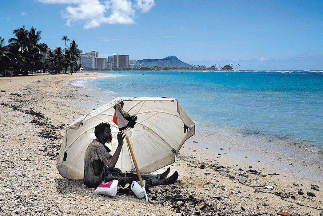 A homeless man drinks water while sitting on the beach at Ala Moana Beach Park located near Waikiki in Honolulu in 2015. (AP Photo/Jae C. Hong)