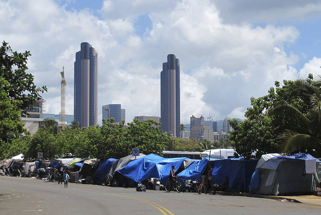 People camp out on a sidewalk in the Kakaako neighborhood of Honolulu in 2015. (AP Photo/Audrey McAvoy)