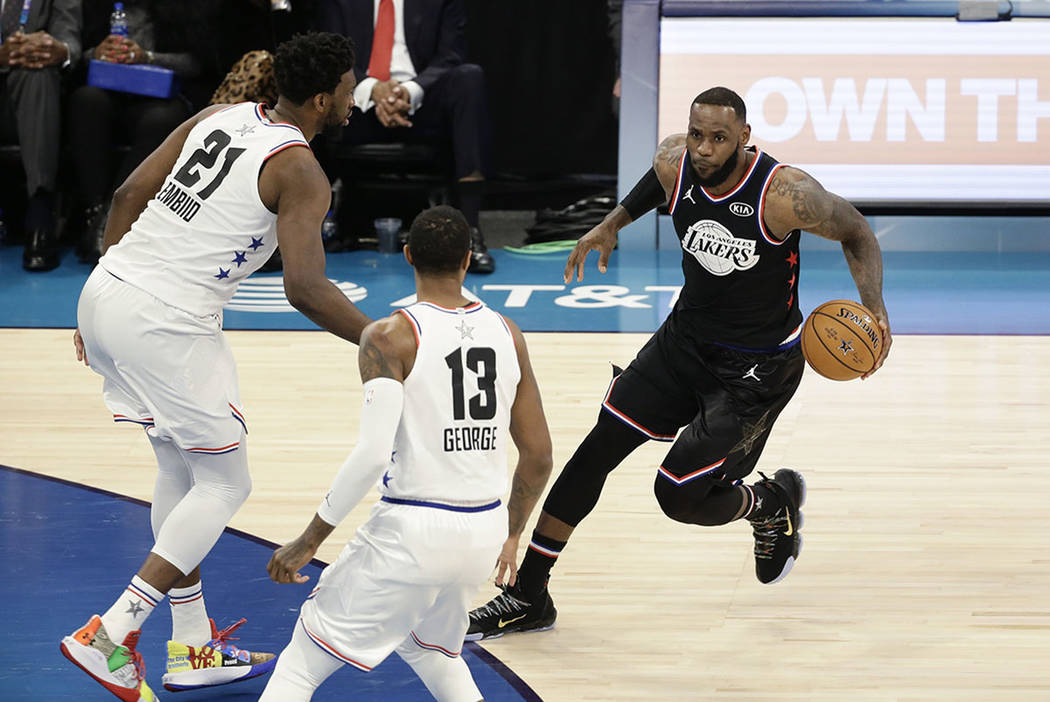Team LeBron's LeBron James, of the Cleveland Cavaliers works against Team Giannis' Paul George, of the Oklahoma City Thunder, and Team Giannis' Joel Embiid, of the Philadelphia 76ers, during the s ...