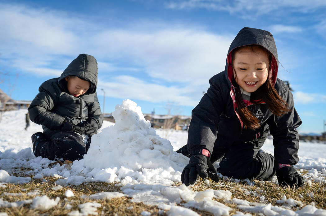 Tenley Chou, 5, right, reaches for a pile of snow as she builds a snowman with her brother Jace Chou, 7, left, at Fox Hill Park in the Summerlin area of Las Vegas, Monday, Feb. 18, 2019. (Caroline ...