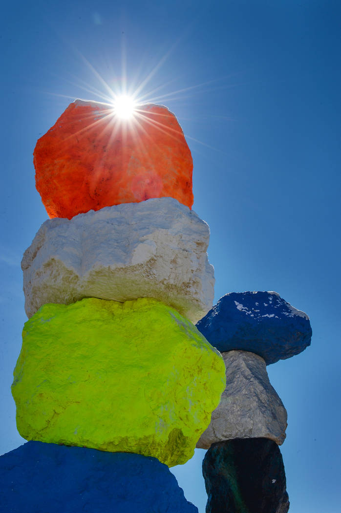 The sun peers over one of the rock structures at the Seven Magic Mountains in Clark County, Monday, Feb. 18, 2019. (Caroline Brehman/Las Vegas Review-Journal) @carolinebrehman