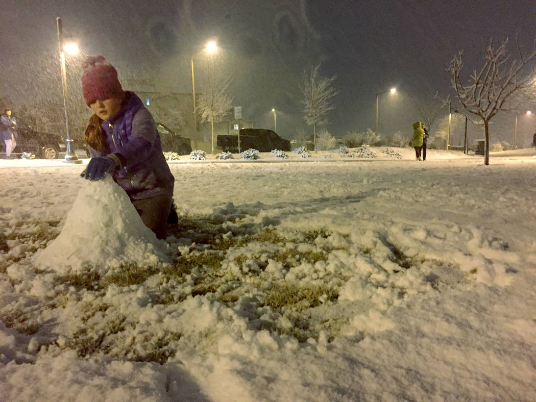Ellie Prindle, 10, a fifth-grader at Givens Elementary School, makes a snowman Sunday night, Feb.17, 2019, at Fox Hill Park in Summerlin. (Marian Green/Las Vegas Review-Journal)