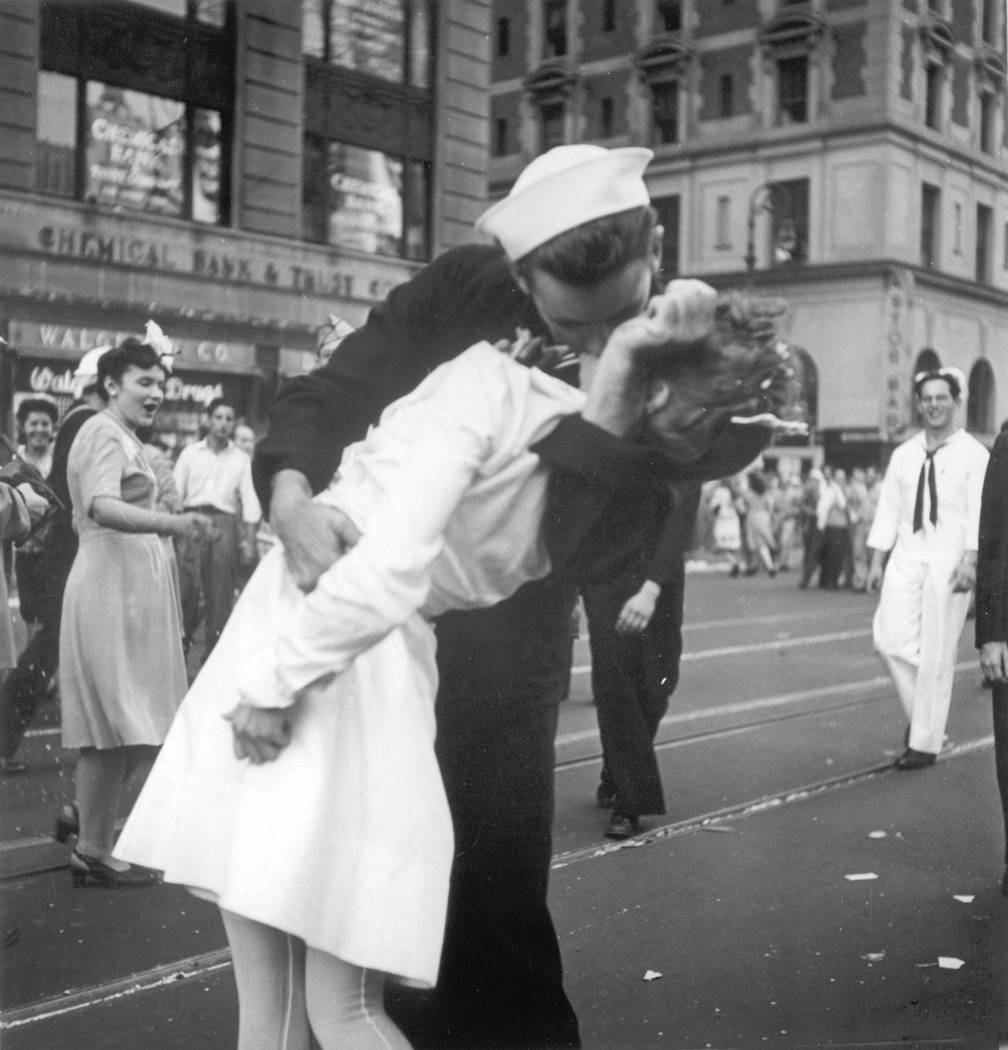 In this Aug. 14, 1945 file photo provided by the U.S. Navy, a sailor and a woman kiss in New York's Times Square, as people celebrate the end of World War II. The sailor, George Mendonsa, has died ...
