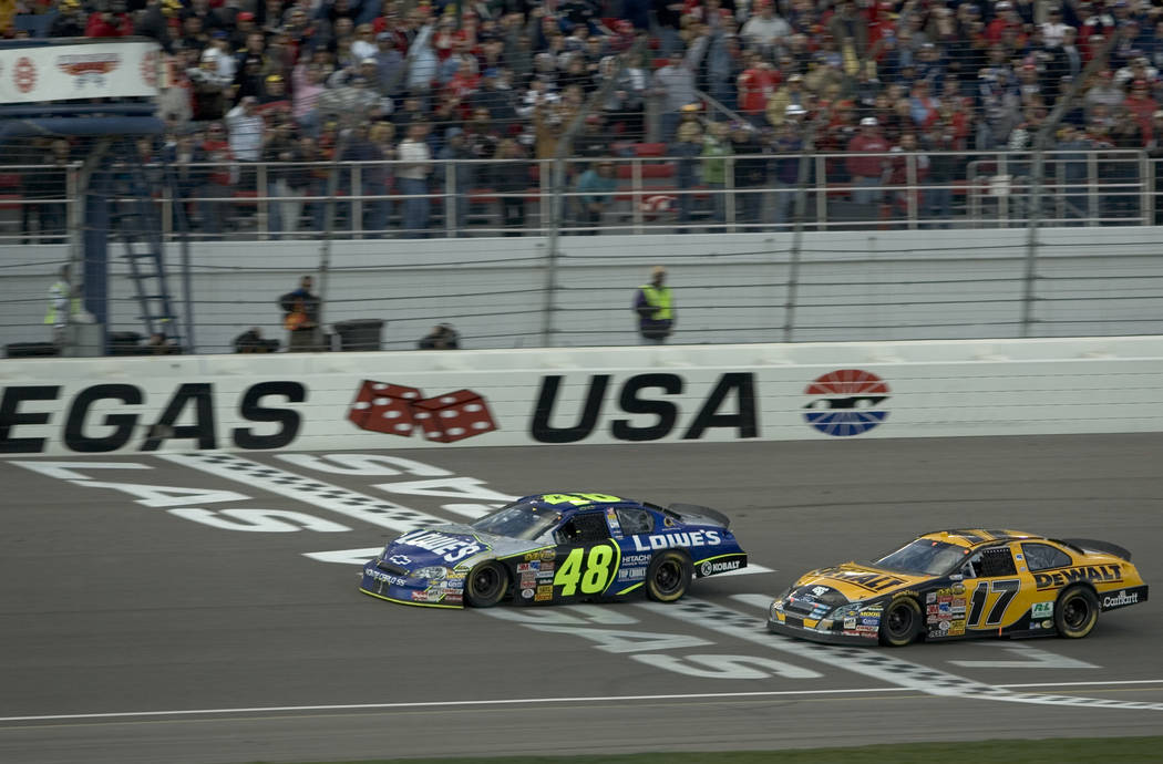 Jimmie Johnson takes the checkered flag a few feet ahead of Matt Kenseth in the NASCAR Nextel Cup UAW-DaimlerChrysler 400 at Las Vegas Motor Speedway Sunday, March 12, 2006. K.M. CANNON/REVIEW-JOURNAL