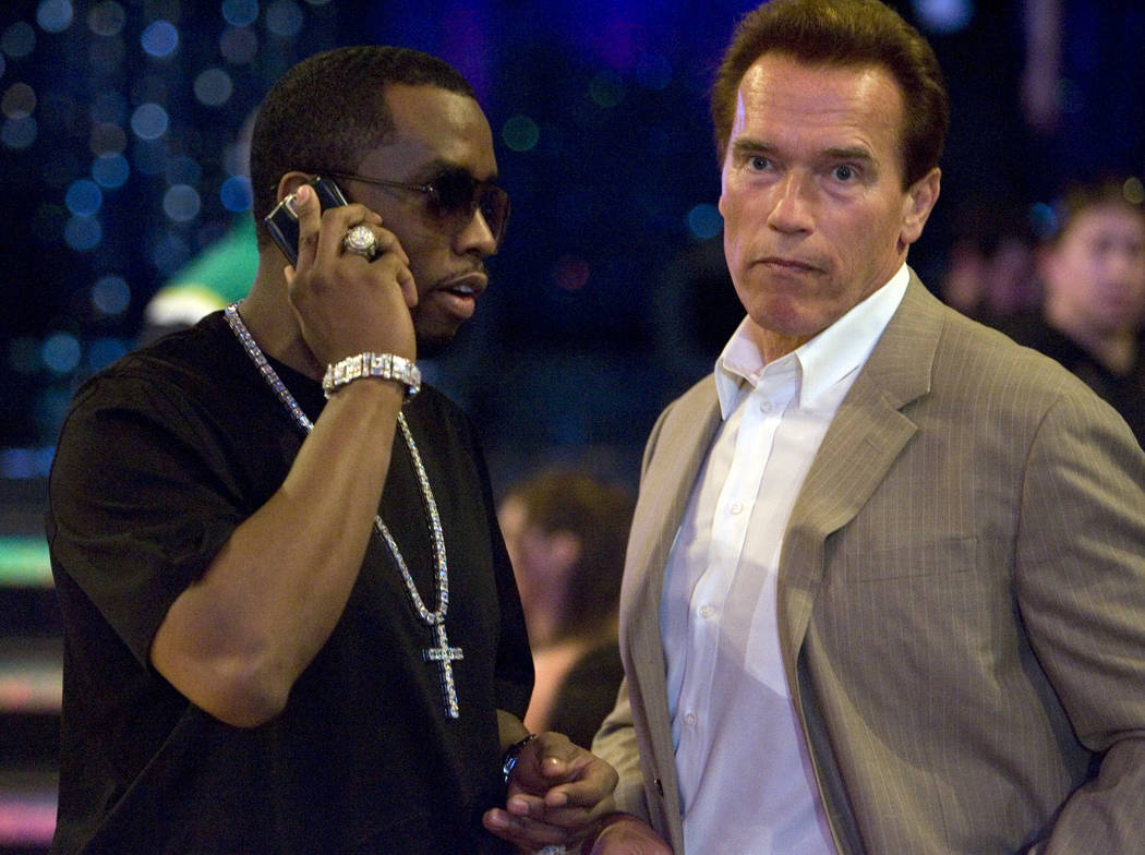"""Sean """"P. Diddy"""" Combs, left, takes a call while chatting with California Gov. Arnold Schwartzeneger before the start of the NBA All-Star Game at the Thomas & Mack Center Sunday, Feb. 18, 2007. K. ..."""