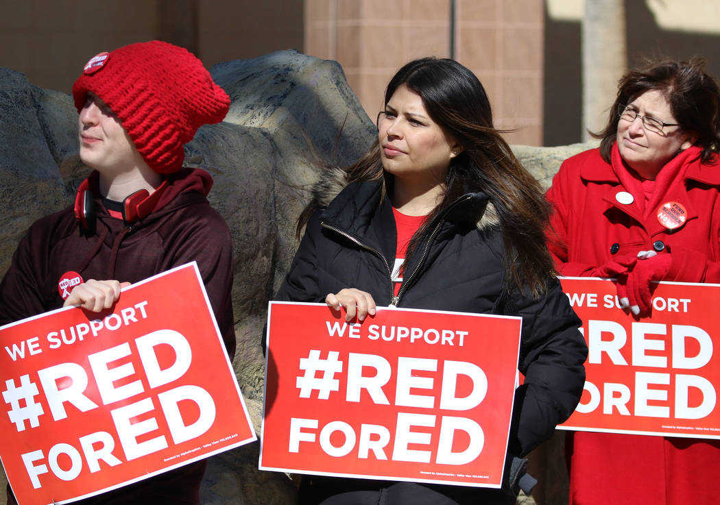 Alec Miller, left, Alicia Norman and Jana Pleggenkuhle, right, hold signs as they demonstrate their support for the ''Red for Ed'' movement outside of the Grant Sawyer Building on Monday, Feb. 18, ...