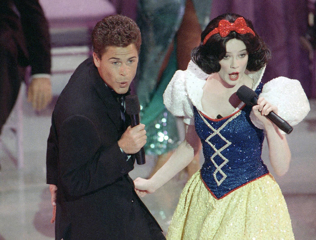 Actor Rob Lowe croons a tune to Snow White during the opening number for the 61st Academy Awards presentation in Los Angeles on March 30, 1989. (AP Photo/ Reed Saxon, File)