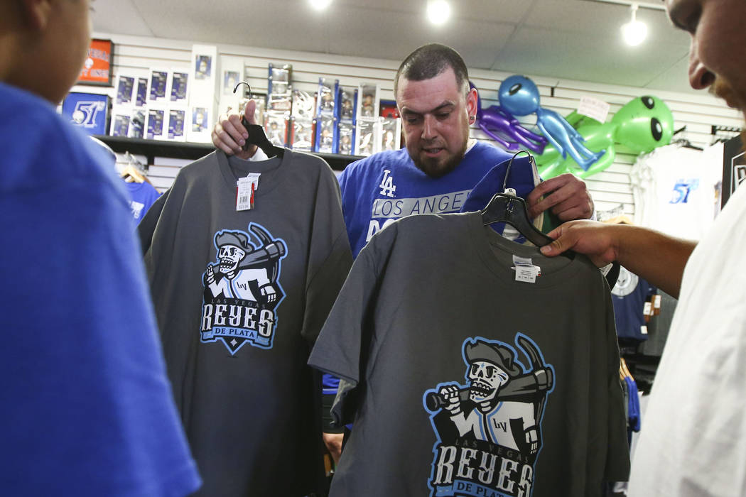 "Jesus Gonzalez, center, checks out shirts featuring the special Las Vegas 51s ""Reyes de Plata"" (Silver Kings) name, part of a new Minor League Baseball initiative, at the team store at C ..."