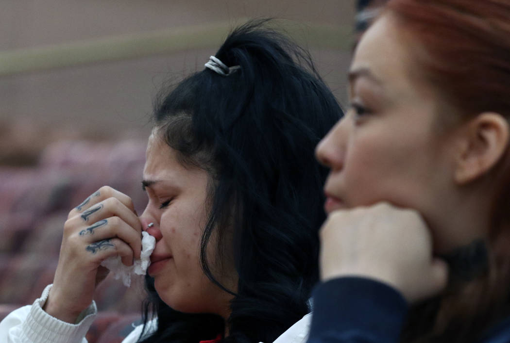 Amber Bustillos, left, a fiance of Junior Lopez, a man fatally shot by Las Vegas police in April, weeps as her friend Carla Varela looks on during a public review of Lopez death on Thursday, Feb. ...