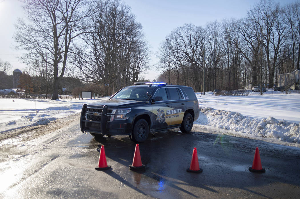 Kent County Sheriff personnel investigate the scene of a fatal shooting near the corner of 19 Mile NE and Division Avenue NE at a property on Monday, Feb. 18, 2019, near Cedar Springs, Mich. (Nei ...