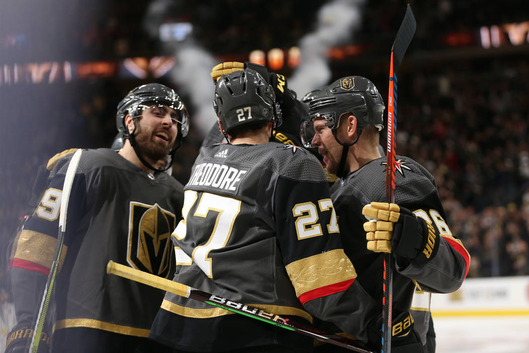 Vegas Golden Knights defenseman Shea Theodore (27) celebrates his score with right wing Alex Tuch (89) and center Paul Stastny (26) during the third period of an NHL hockey game at T-Mobile Arena ...