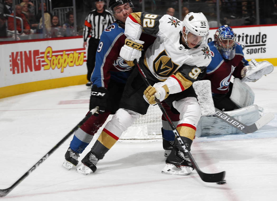 Vegas Golden Knights left wing Tomas Nosek, front, moves past Colorado Avalanche defenseman Samuel Girard to put a shot on goaltender Semyon Varlamov, back, in the second period of an NHL hockey g ...