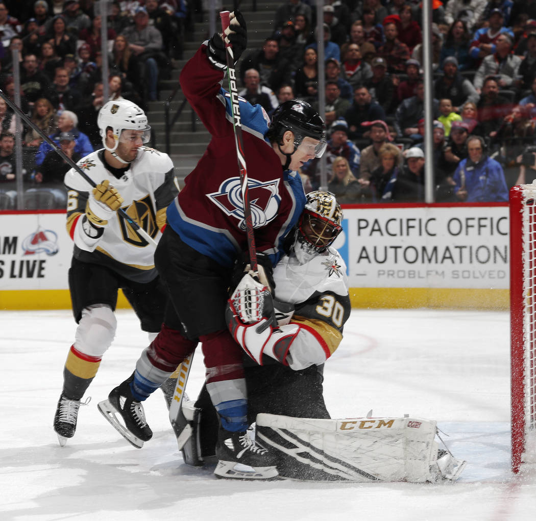 Colorado Avalanche left wing Matt Calvert, center, runs into Vegas Golden Knights goaltender Malcolm Subban after redirecting shot into the net for a goal as defenseman Colin Miller looks on in th ...