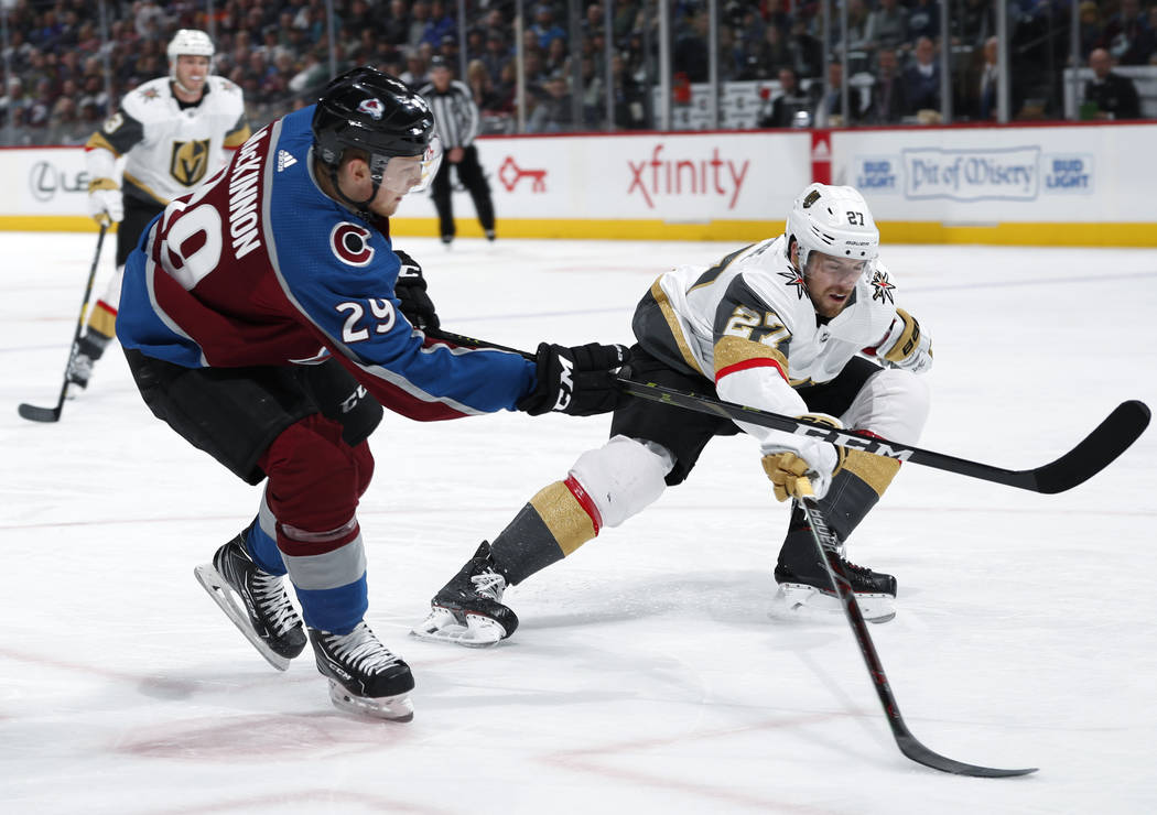 Colorado Avalanche center Nathan MacKinnon, left, fires the puck on the net past Vegas Golden Knights defenseman Shea Theodore in the third period of an NHL hockey game Monday, Feb. 18, 2019, in D ...